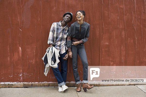 Ein junges Paar  das sich an eine Wand lehnt.