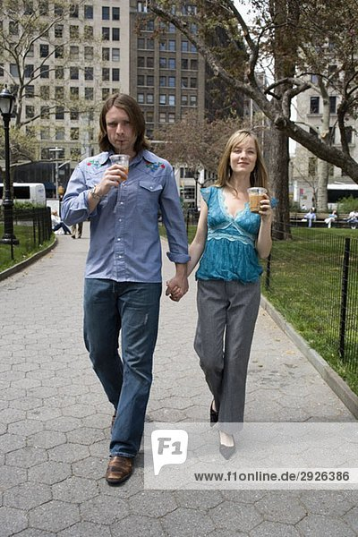 A young couple walking through a city park holding hands  Central Park  New York City