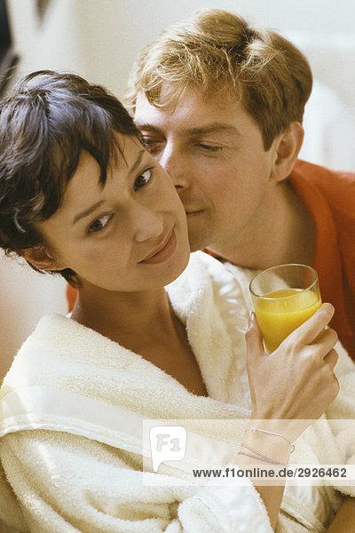 Frau hält ein Glas Orangensaft  der Mann küsst ihre Wange.