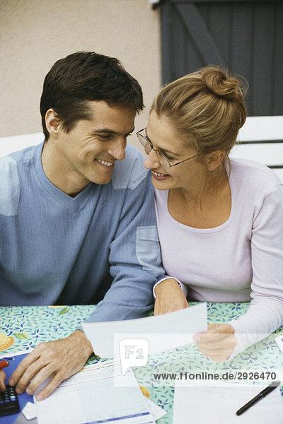 Ein Paar sitzt am Tisch und diskutiert über die Finanzen.