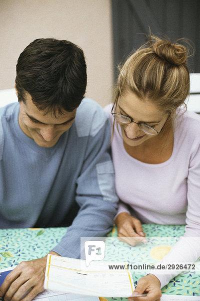 Ein Paar sitzt am Tisch und bezahlt Rechnungen.