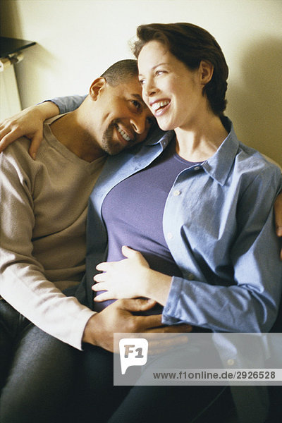 Couple sitting together  with hands on woman's pregnant belly