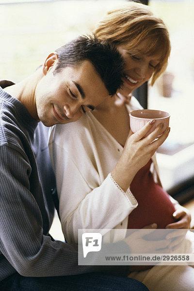 Mann umarmt schwangere Frau  Hände auf dem Bauch  Frau trinkt Tee