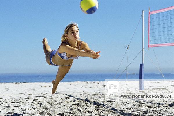 Frauen beim Beachvolleyball  Tauchen zum Ball fangen