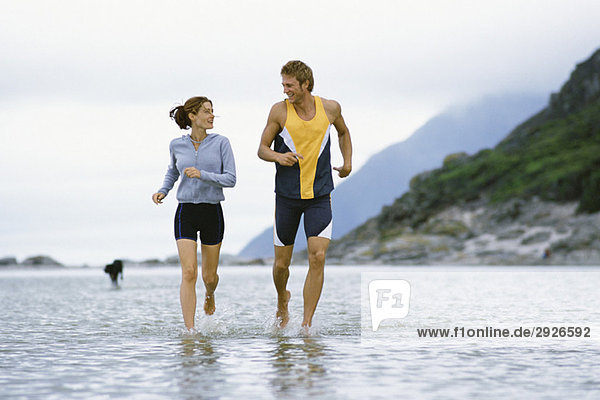 Young couple running together through shallow water near shore
