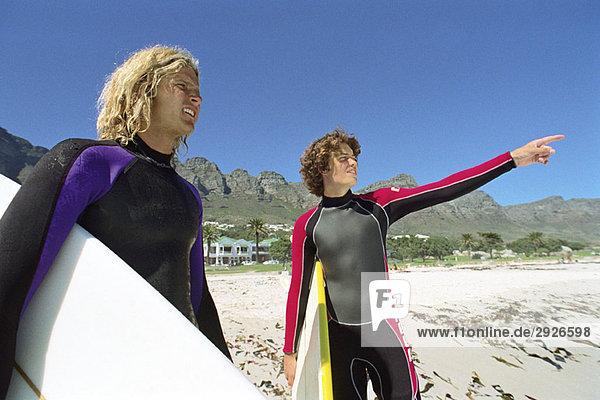 Surfer am Strand  einer zeigt auf Distanz