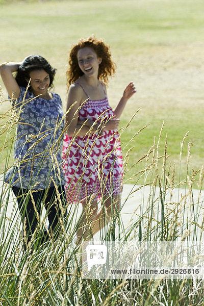 Zwei junge Frauen  die im Freien Arm in Arm gehen  beide lachend.