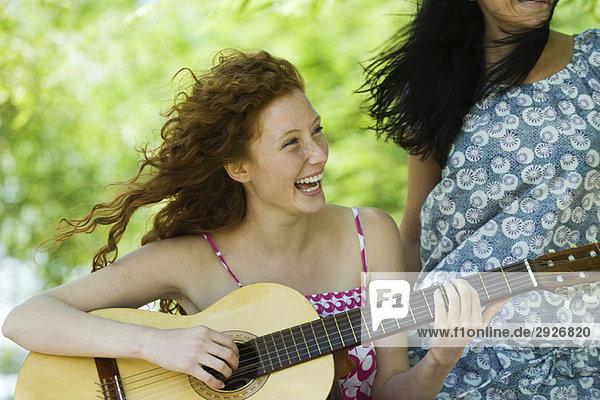 Junge Frau  die im Freien Akustikgitarre spielt  lacht