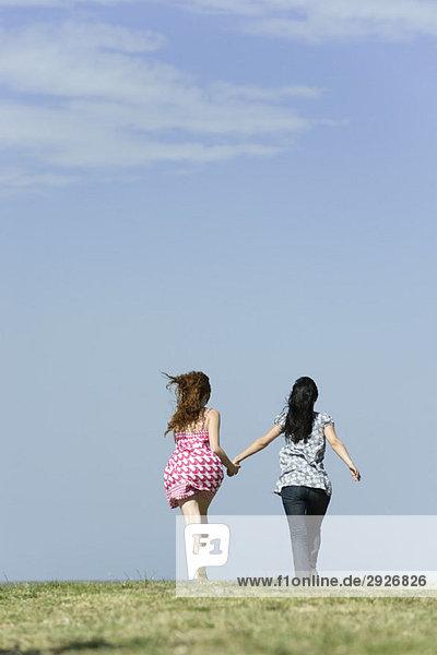 Zwei junge Frauen laufen Hand in Hand  Rückansicht