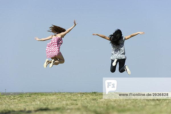 Zwei junge Frauen beim Springen im Freien  Rückansicht
