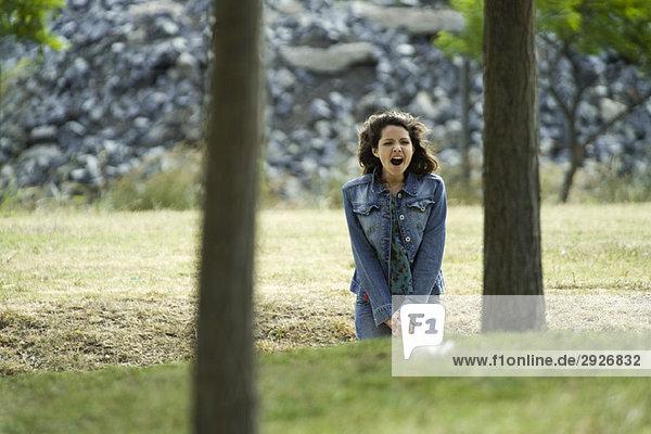 Junge Frau im Freien sitzend mit weit geöffnetem Mund
