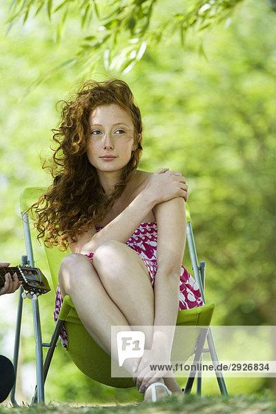 Junge Frau im Klappstuhl im Freien sitzend  wegschauend