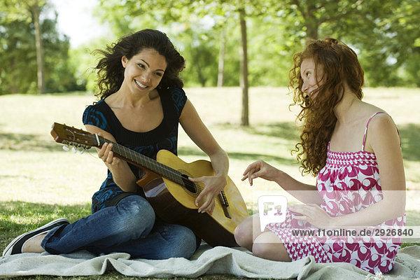 Zwei junge Frauen sitzen auf einer Decke im Freien  eine spielt Akustikgitarre.