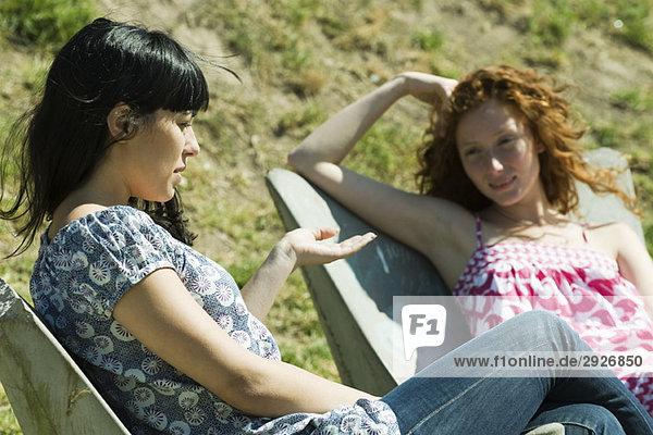 Zwei junge Frauen  die draußen sitzen und reden.