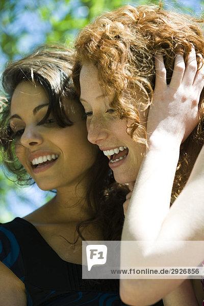 Zwei junge Frauen  Wange an Wange  lachend