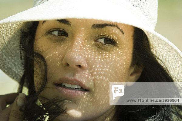 Junge brünette Frau mit Sonnenhut  Nahaufnahme