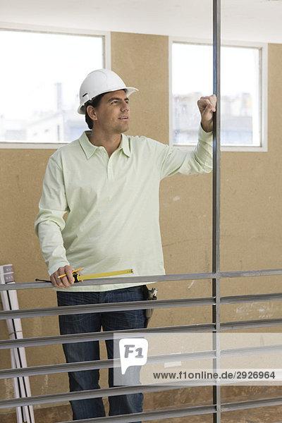 Mann hält Maßband  trägt einen Schutzhelm  steht am Geländer und schaut weg.