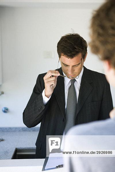 Geschäftsmann prüft Dokument  assoziiert geduldig wartend