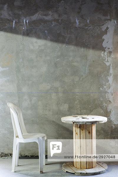Plastikstuhl-Set vor Holzrollentisch im unfertigen Raum