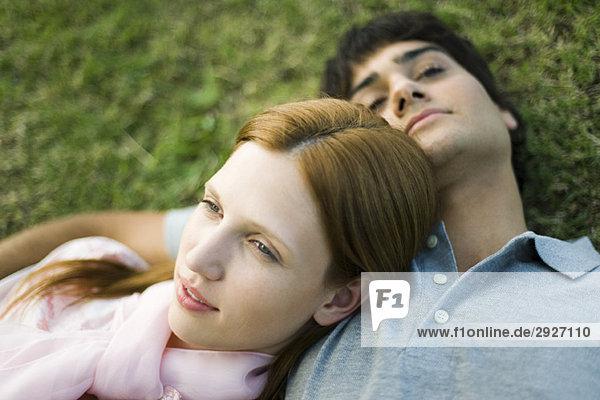 Junges Paar auf dem Rasen liegend  Portrait