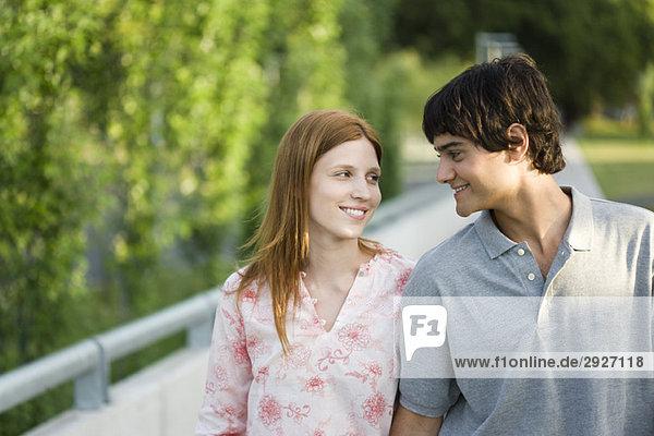 Junges Paar  das gemeinsam im Freien spazieren geht und sich anlächelt
