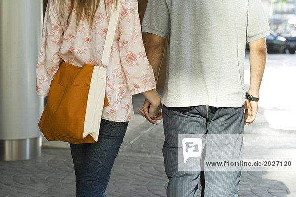Junges Paar geht Hand in Hand auf Bürgersteig  Rückansicht  abgeschnitten