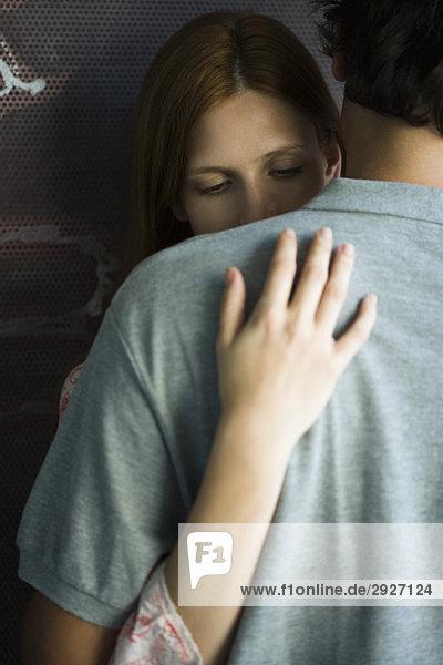 Junges Paar umarmt steif  Frau schaut nach unten