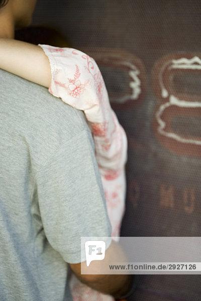Paar an der Wand umarmend  abgeschnitten