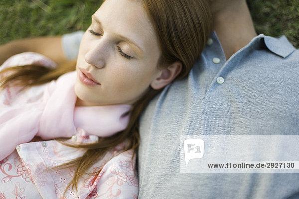 Junges Paar schläft auf dem Boden  der Kopf der Frau ruht auf der Brust des Mannes.