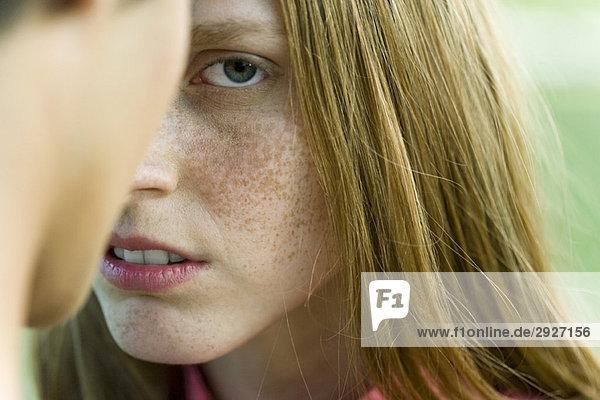Junge Frau vor dem Mann  vorsichtig in die Kamera starrend  abgeschnitten