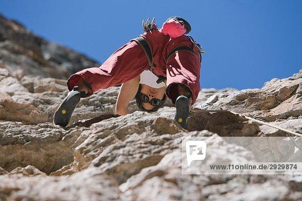 Climber Skalierung eine Felswand