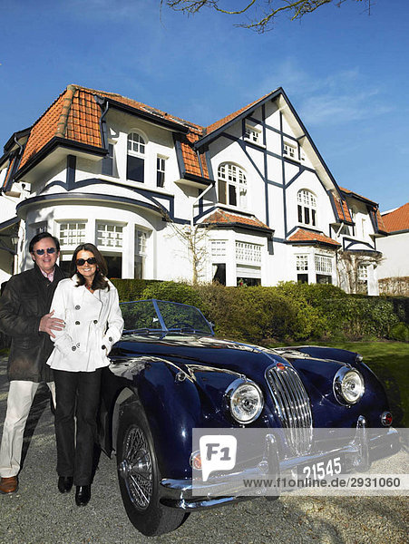 Paar vor ihrem Haus und Auto