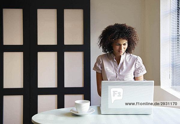 Frau im Café bei der Arbeit am Laptop