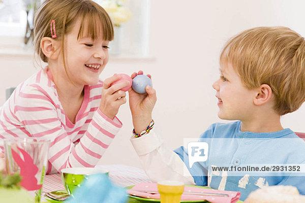 Mädchen und Junge malen Eier für Ostern