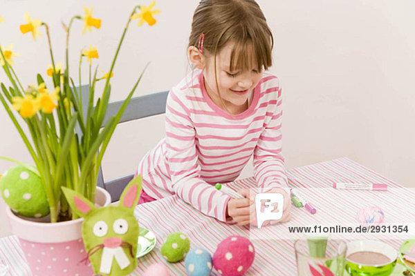 Mädchen malt Eier für Ostern