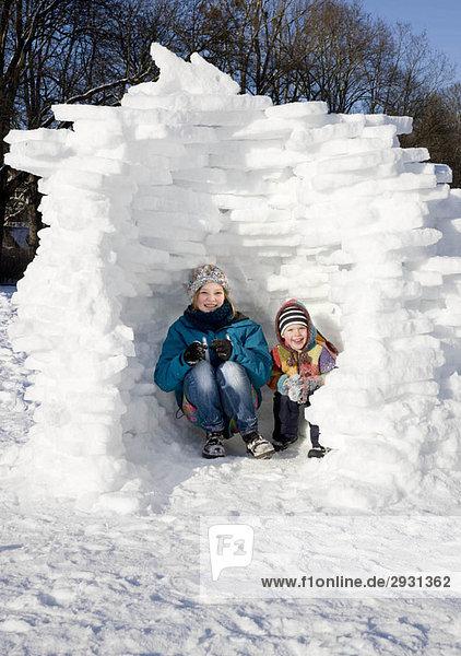 Mädchen und Junge im Iglu im Schnee