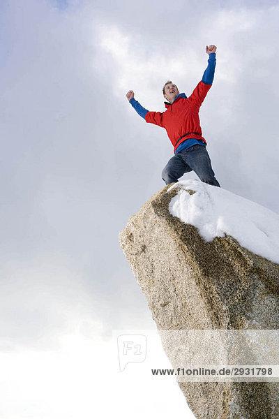Kletterer feiert auf schneebedecktem Gipfel