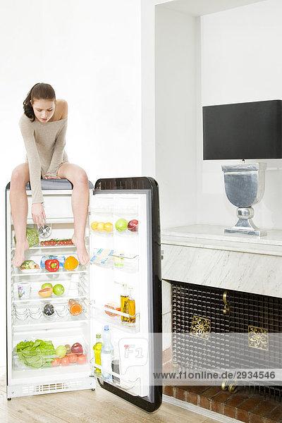 Frau erreichen Essen im Kühlschrank