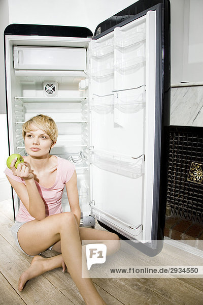 junge Frau neben Emapty Kühlschrank