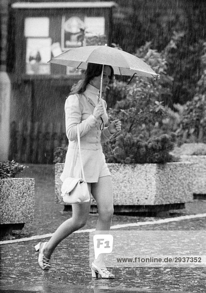 Seventies  black and white photo  weather  rain  young girl under an umbrella  aged 18 to 23 years Seventies, black and white photo, weather, rain, young girl under an umbrella, aged 18 to 23 years