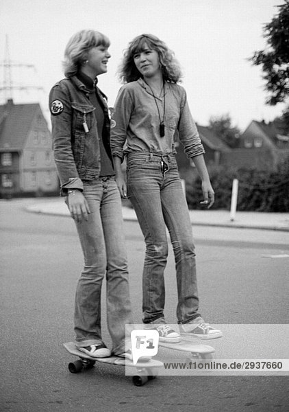 Seventies  black and white photo  people  two young girls on rollerblades drive on the street  jeans suit  jeans trousers  aged 15 to 18 years