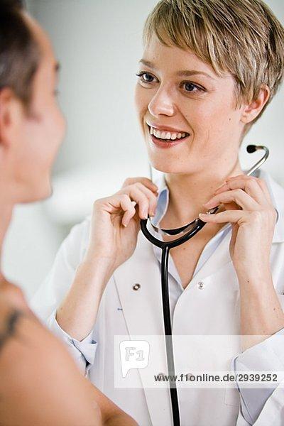 Ein Arzt mit einem Stethoskop auf ein Patient Schweden.