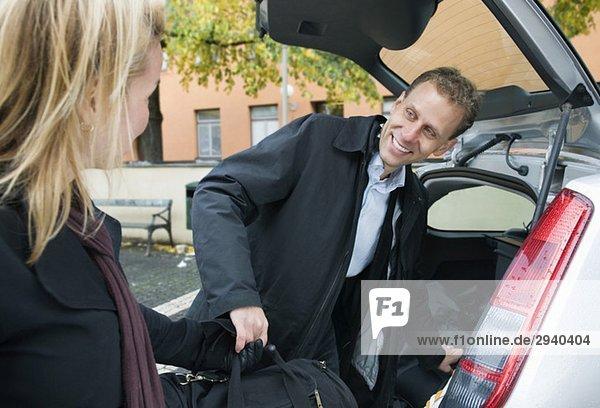 MAn und Frau beim Verladen von Taschen ins Auto