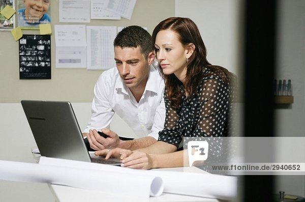 Zwei Leute am Schreibtisch sehen sich den Computer an.