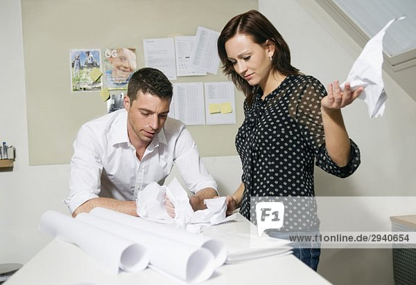 Zwei Leute am Schreibtisch zeigen Frustration.
