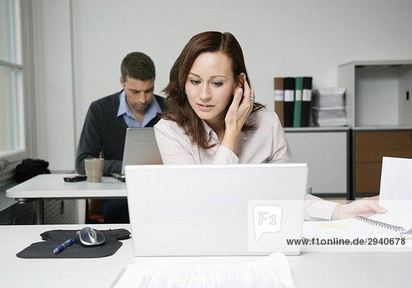 Frau schaut auf Laptop  Kollegin arbeitet im Hintergrund