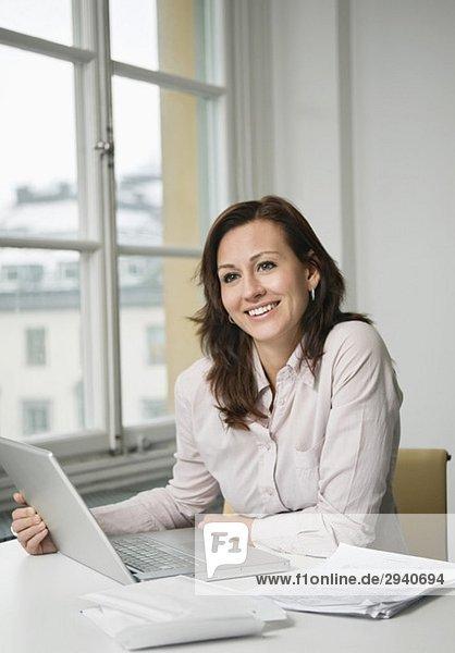 Geschäftsfrau sitzend mit Laptop