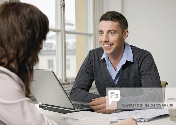Zwei Leute reden am Schreibtisch