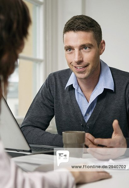Mann im Gespräch mit Frau am Schreibtisch