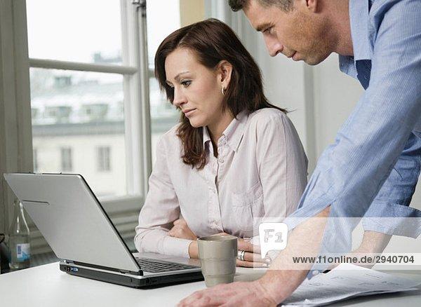 Zwei Leute schauen auf den Laptop